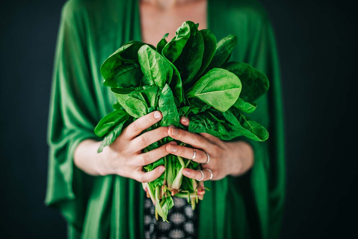 woman in green shirt holding freshly picked spinach