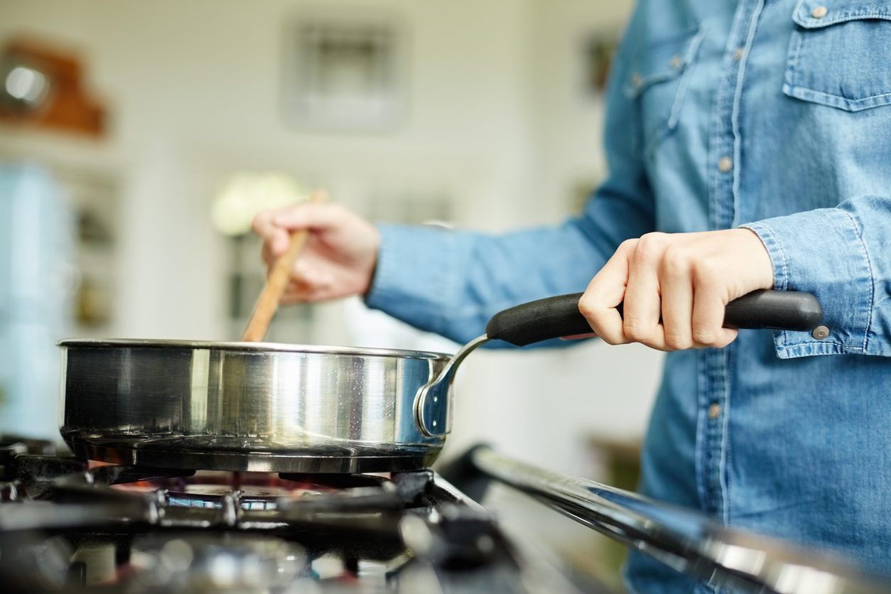 Woman cooking food with the kitchen tools, frying pan and wooden spoon.