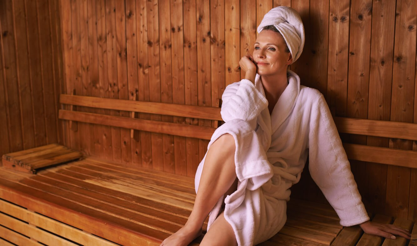 Mature woman in bathrobe in sauna