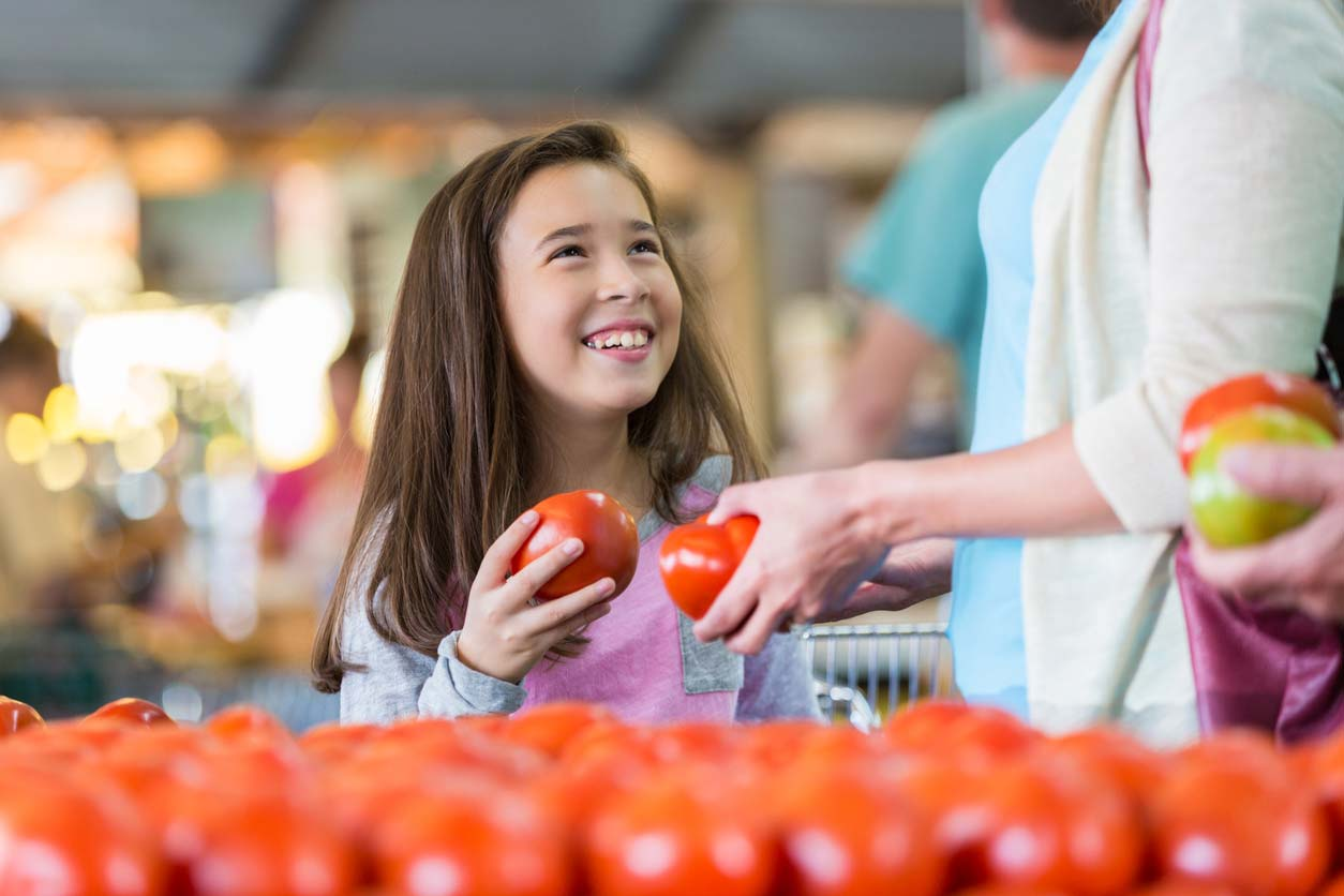 little girl shopping for produce with mother