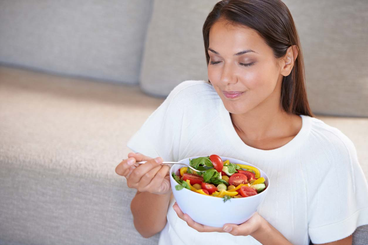 Woman practicing mindful eating and enjoying fresh salad