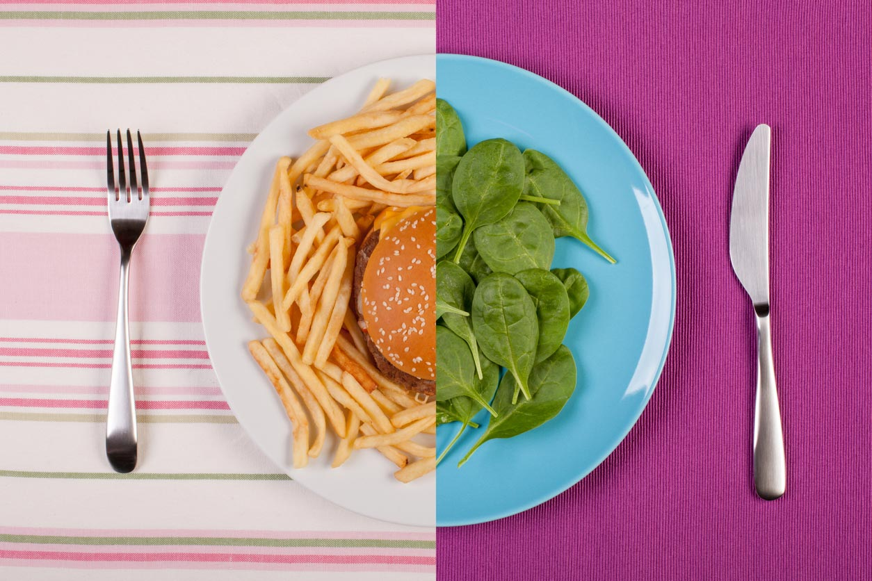 photo split in middle with burger and fries on one side, greens on other