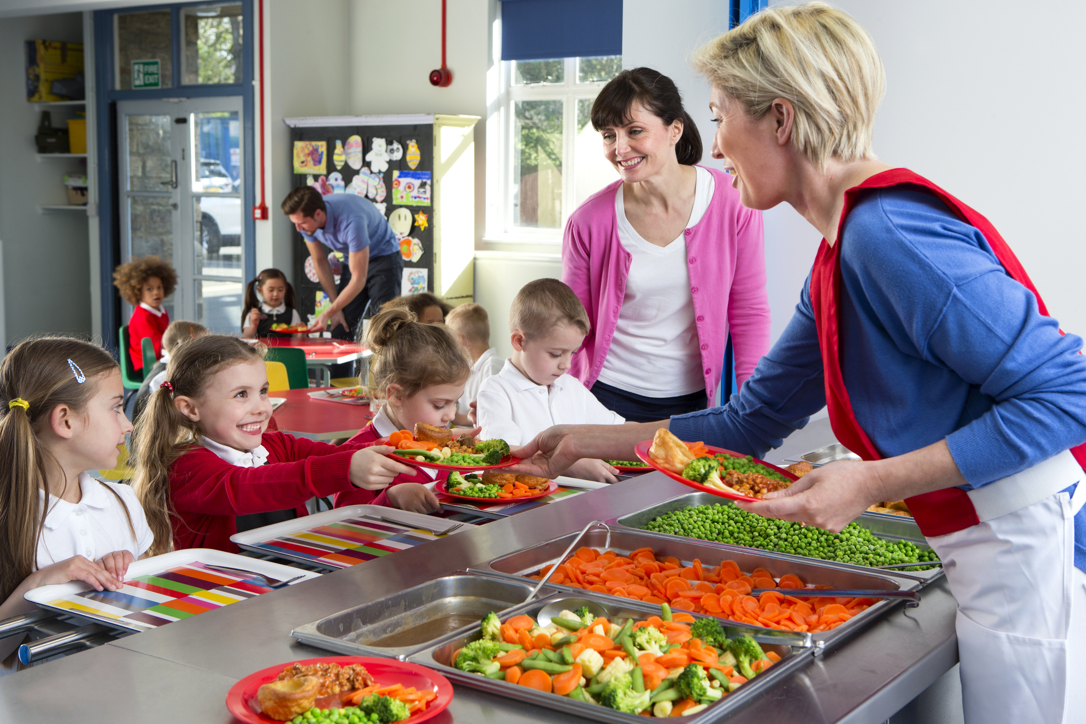 Dinner is served out to children as they line up at a school cafeteria.