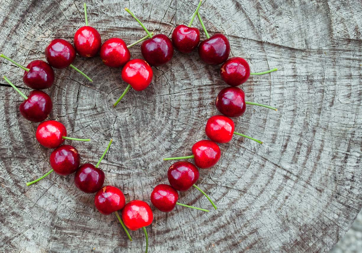 cherries in shape of heart on wooden surface