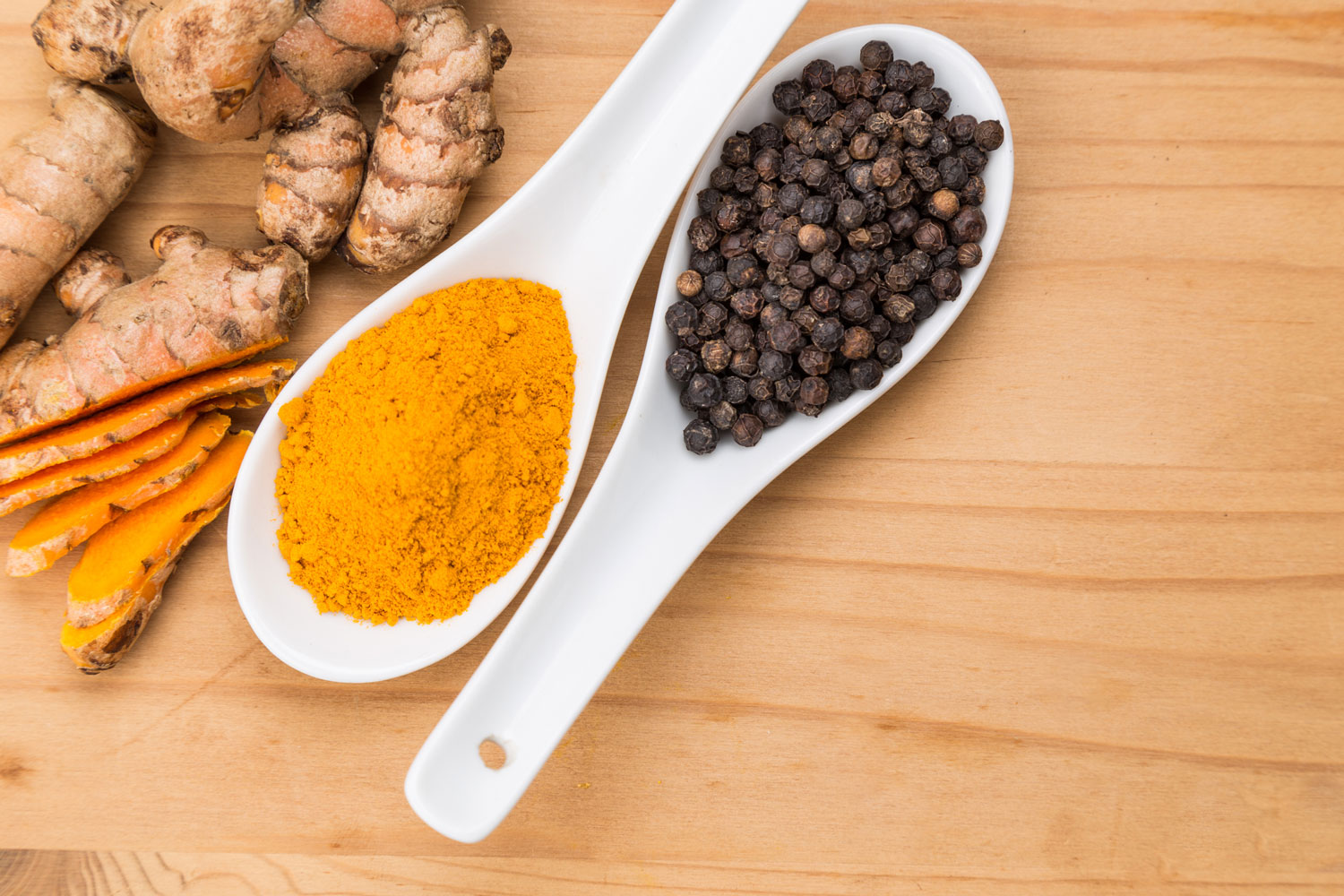 turmeric and black pepper on spoons