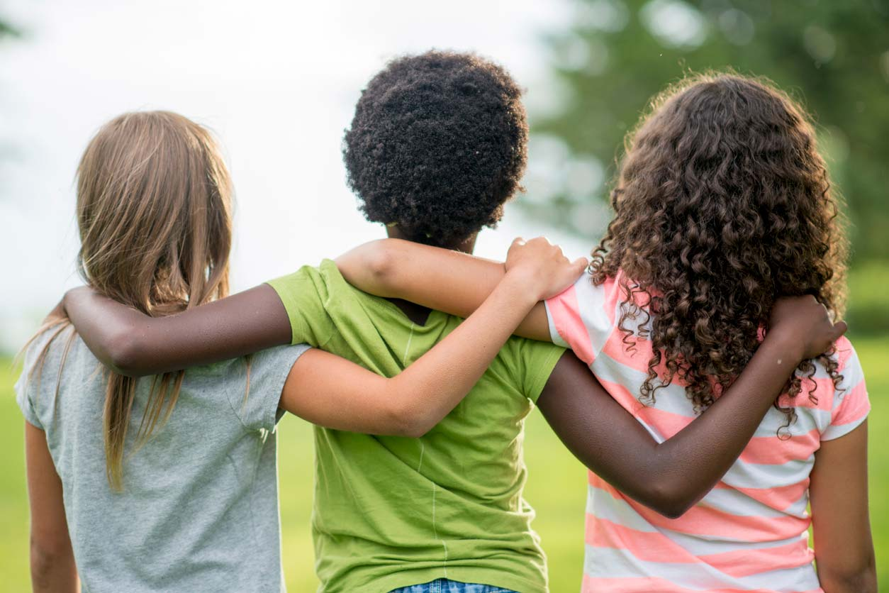 three young multi-racial friends standing together with arms on shoulders