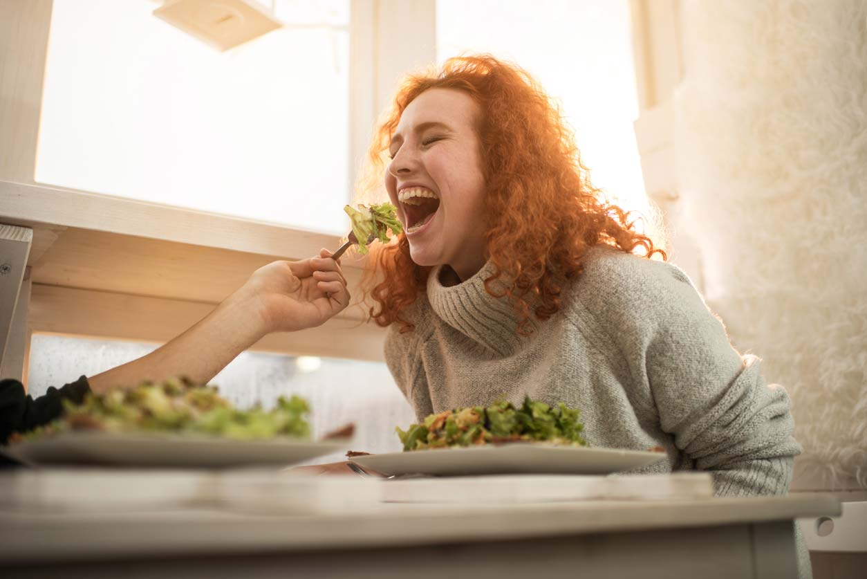 Woman being fed forkful of salad greens