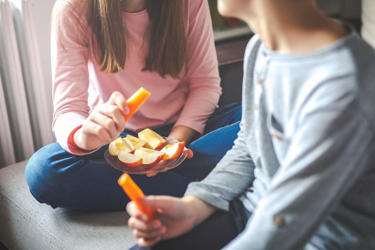 young people eating healthy crunchy snack of apples and carrots