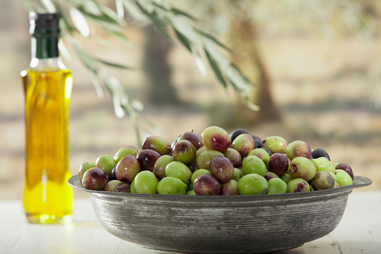 Raw olives and a jar of olive oil