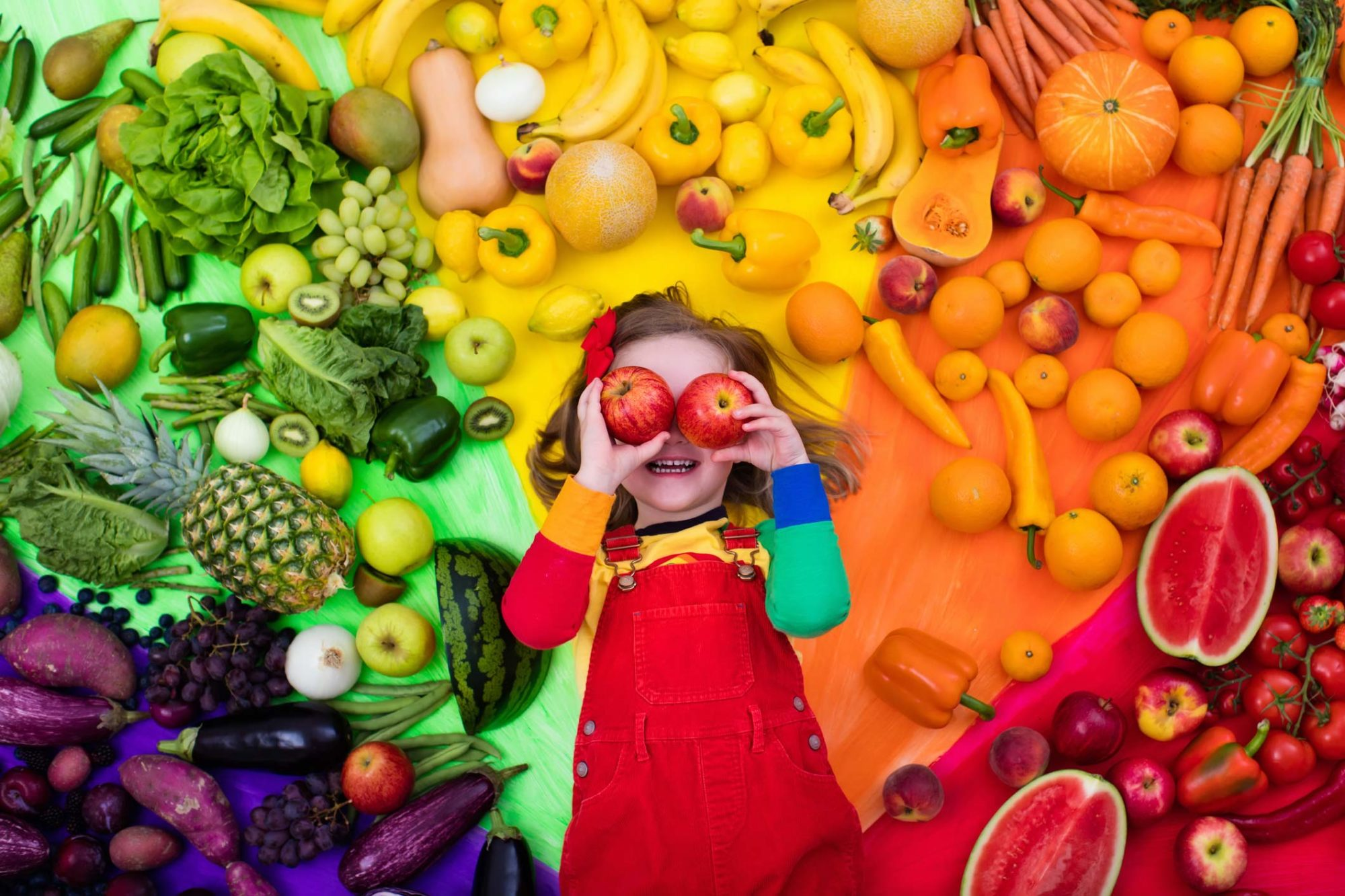 Young girl using apples for eyes surrounded by a rainbow of fruits and vegetables