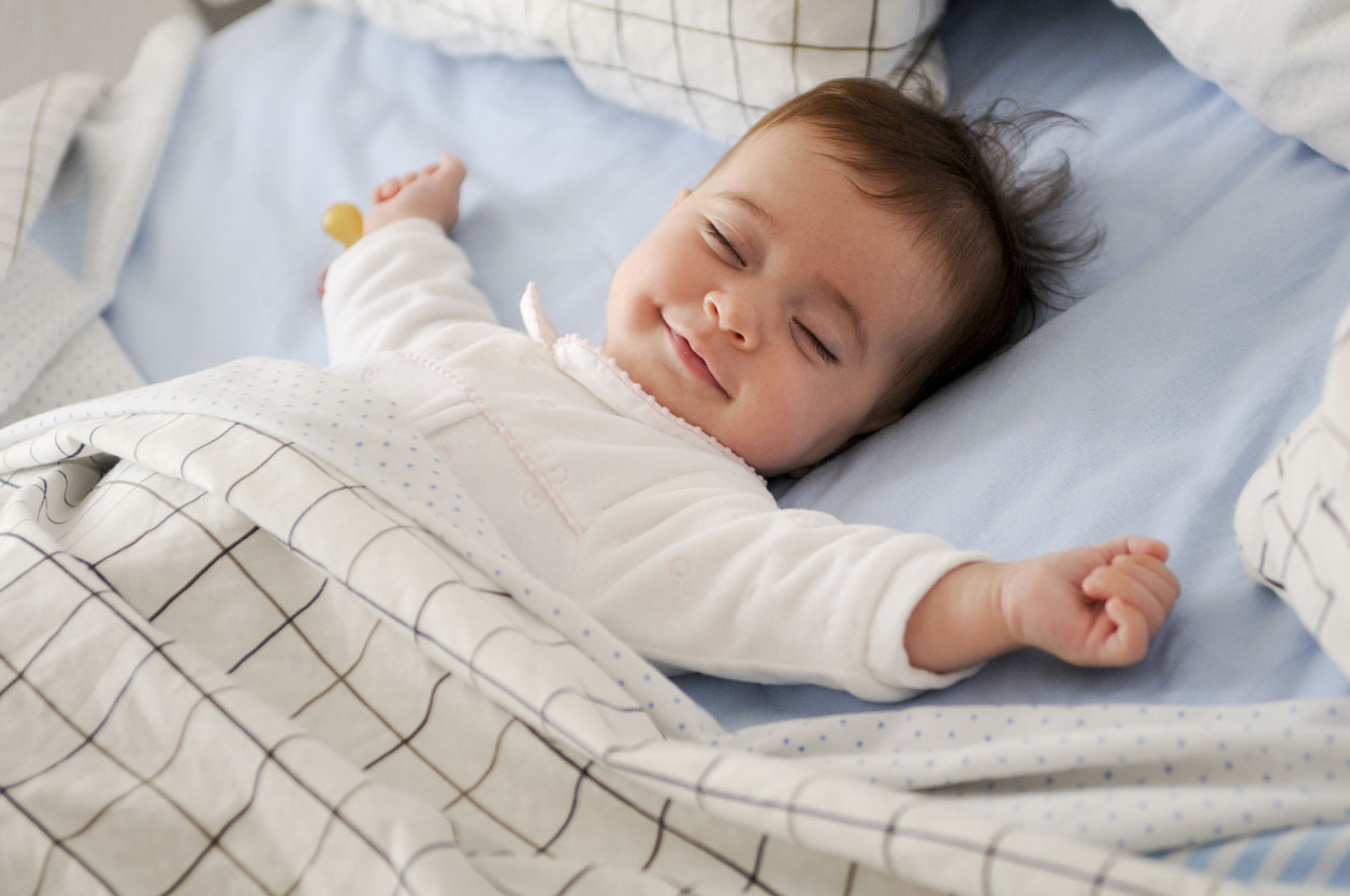 smiling baby girl on bed