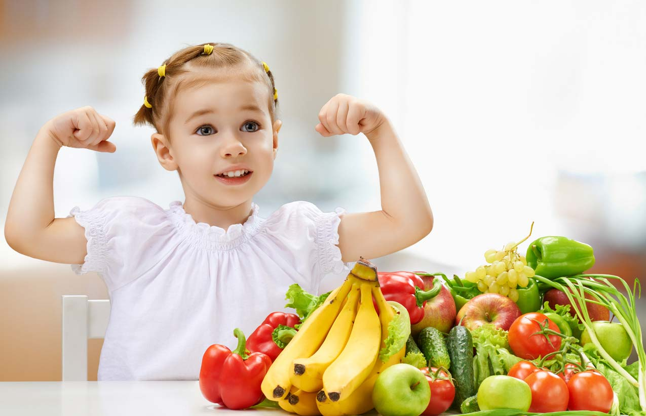 young girl holding up strong arms behind fruits and veggies
