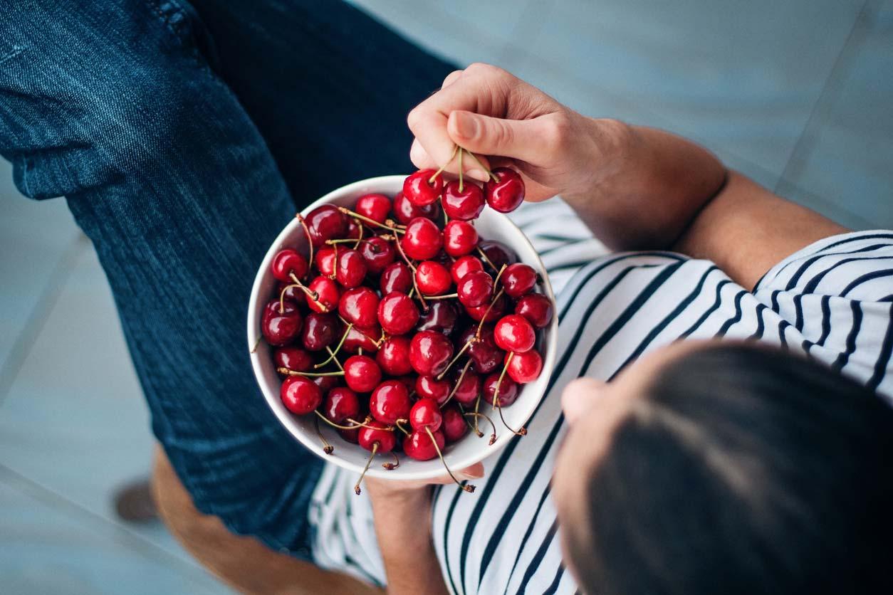 cherries in a bowl - woman enjoying benefits of cherries