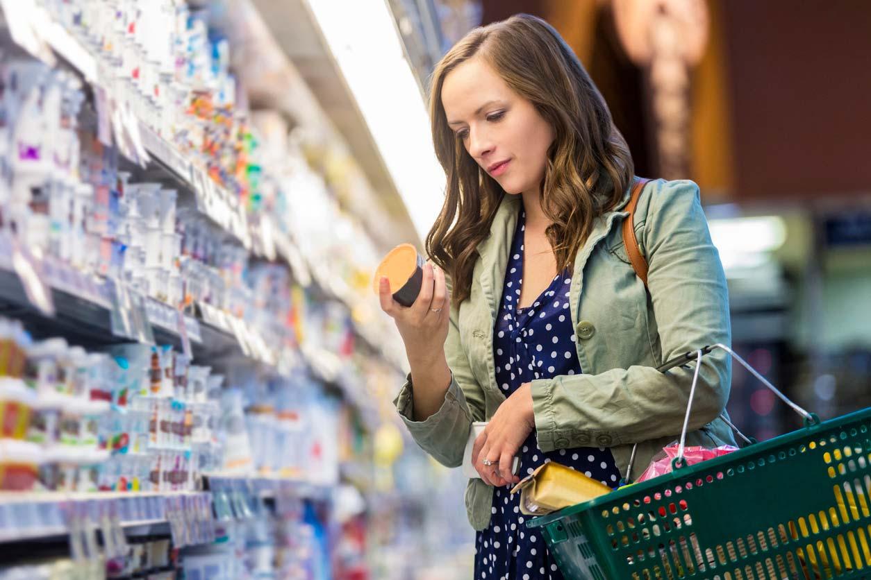 woman reading yogurt food label in grocery store