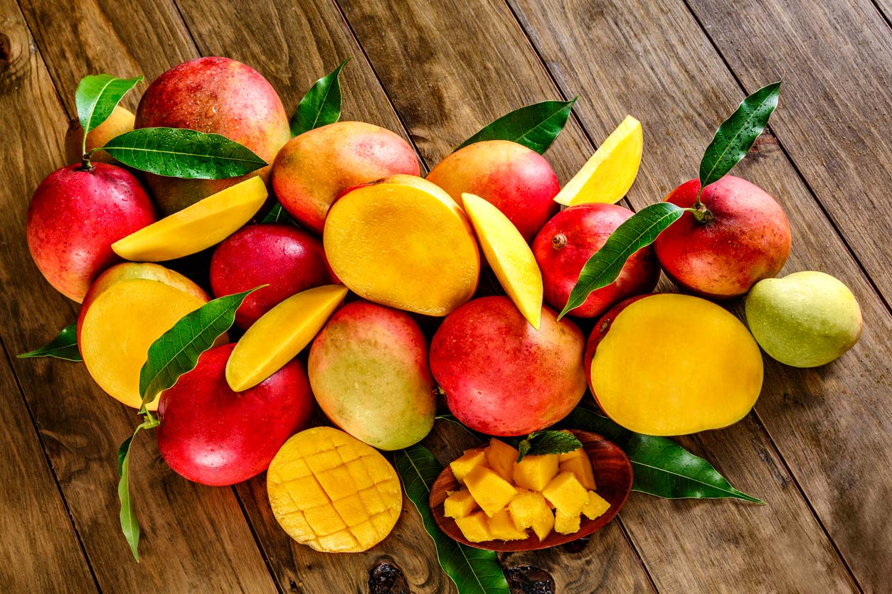 group of ripe mangoes on wooden table