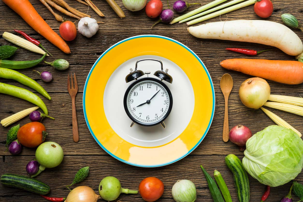 Vegetables surrounding plate with alarm clock