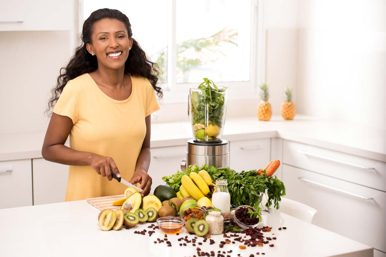 Smiling woman in kitchen getting magnesium health benefits from food