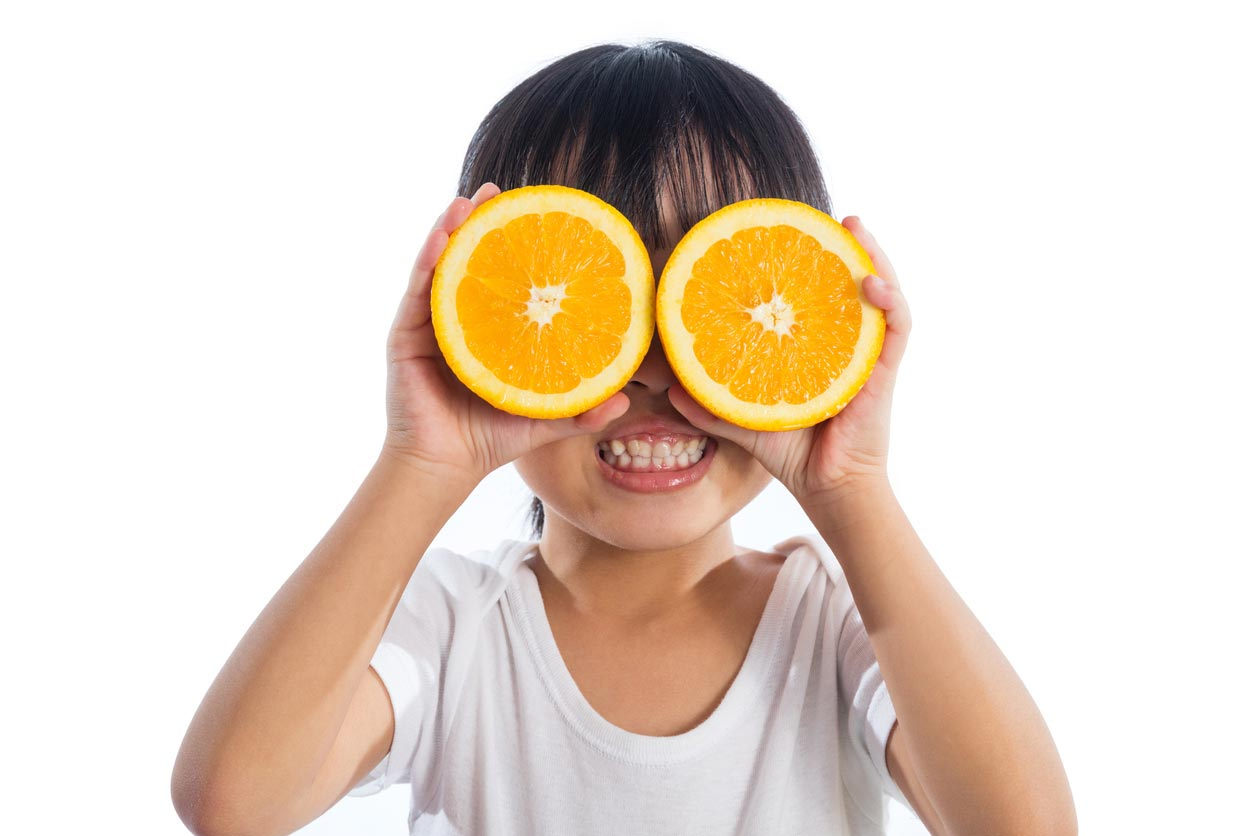 little girl using oranges as glasses