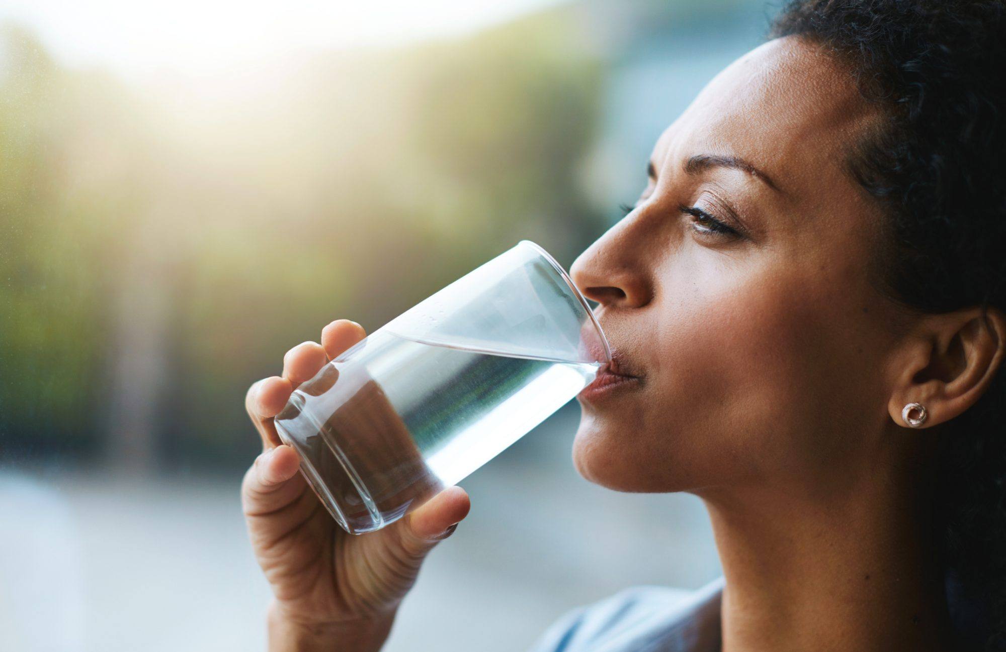 Shot of a woman drinking a glass of water at home