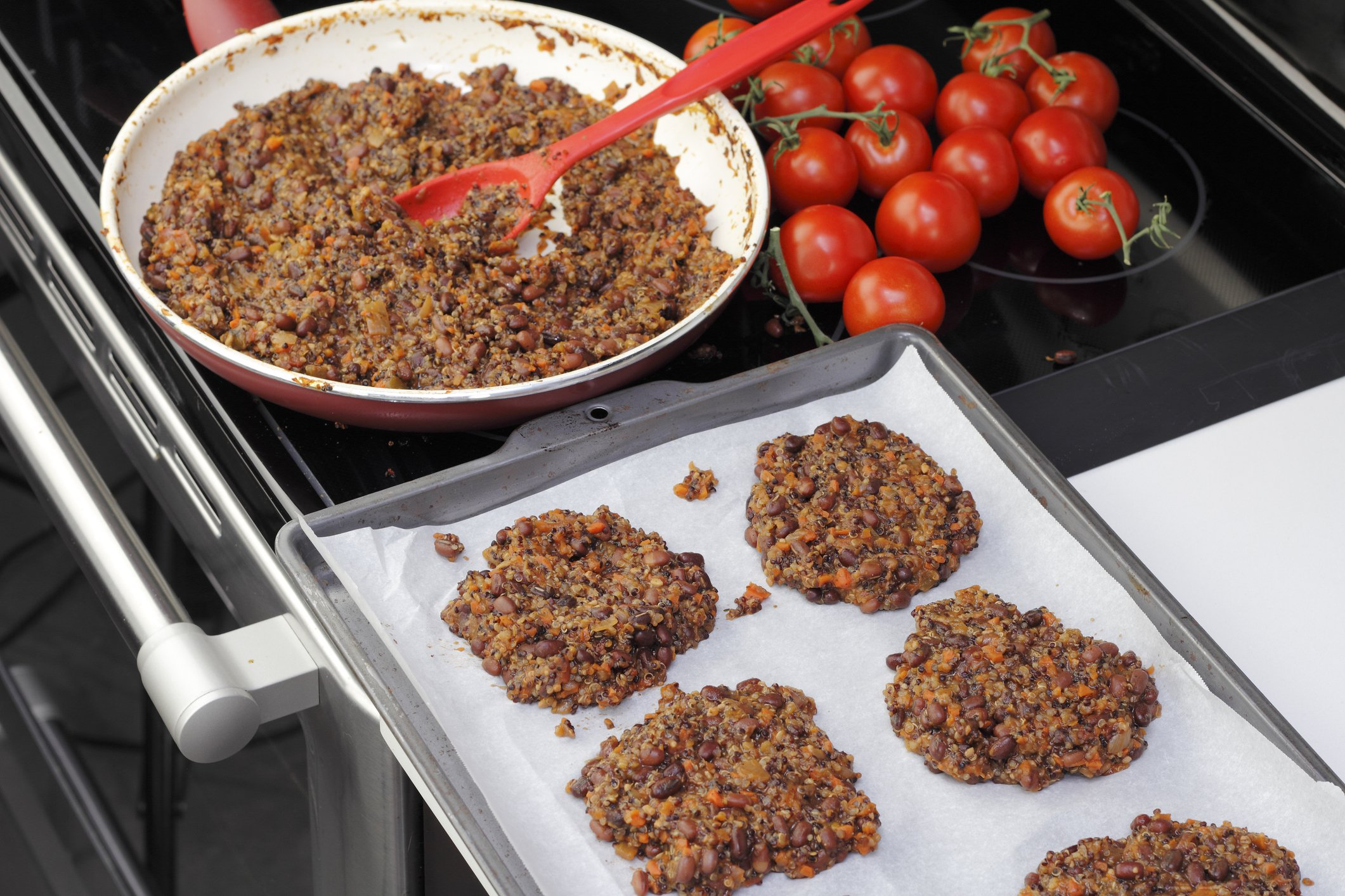 Parchment paper lined cookie sheet with quinoa and three bean veggie burgers ready to be cooked. Preparing tricolor bean and quinoa burgers recipe in the kitchen.