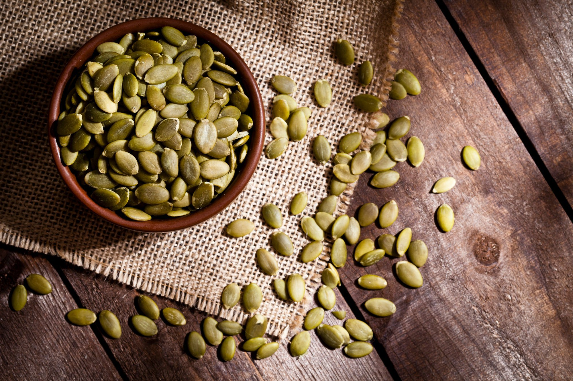 pumpkin seeds in a bowl and on a table