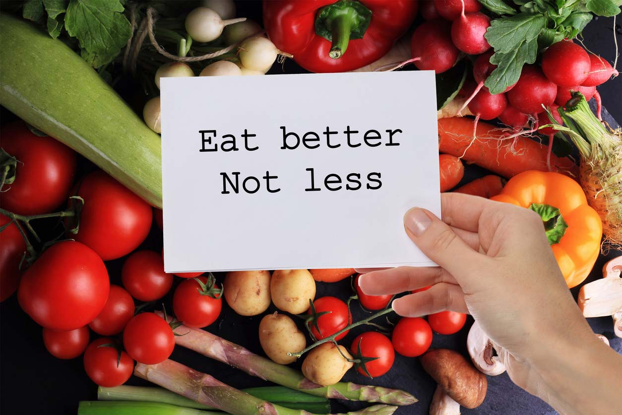 eat better not less inspirational note in front of vegetables