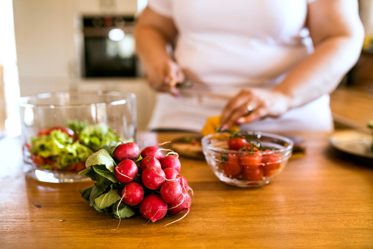 unrecognizable overnight woman at home preparing a delicious healthy vegetable salad