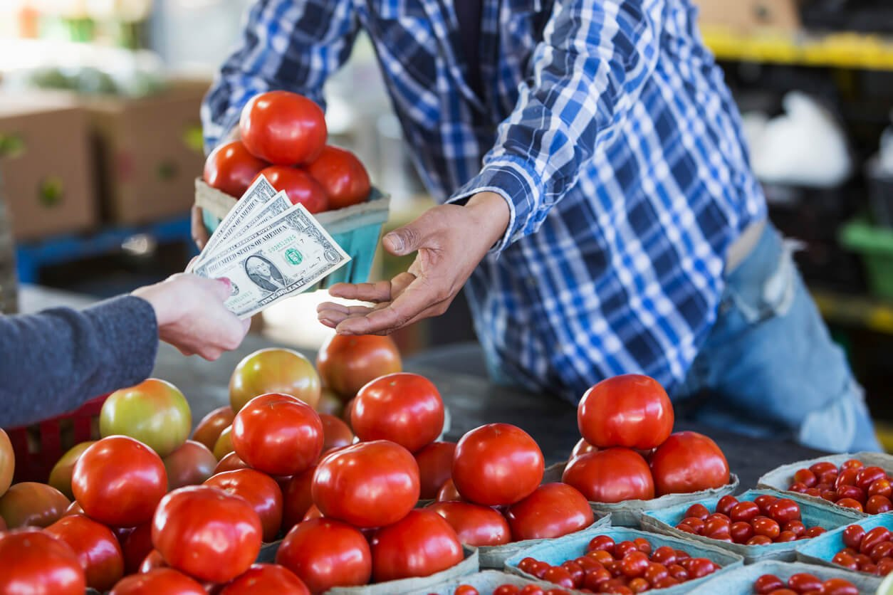 customer paying for tomatoes at produce stand