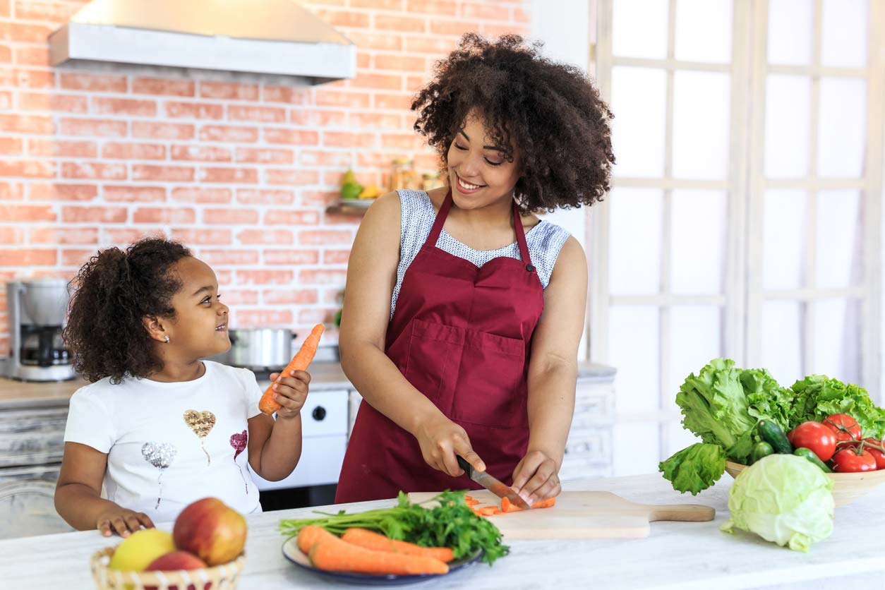 mother and daughter preparing food and learning about nutritional education