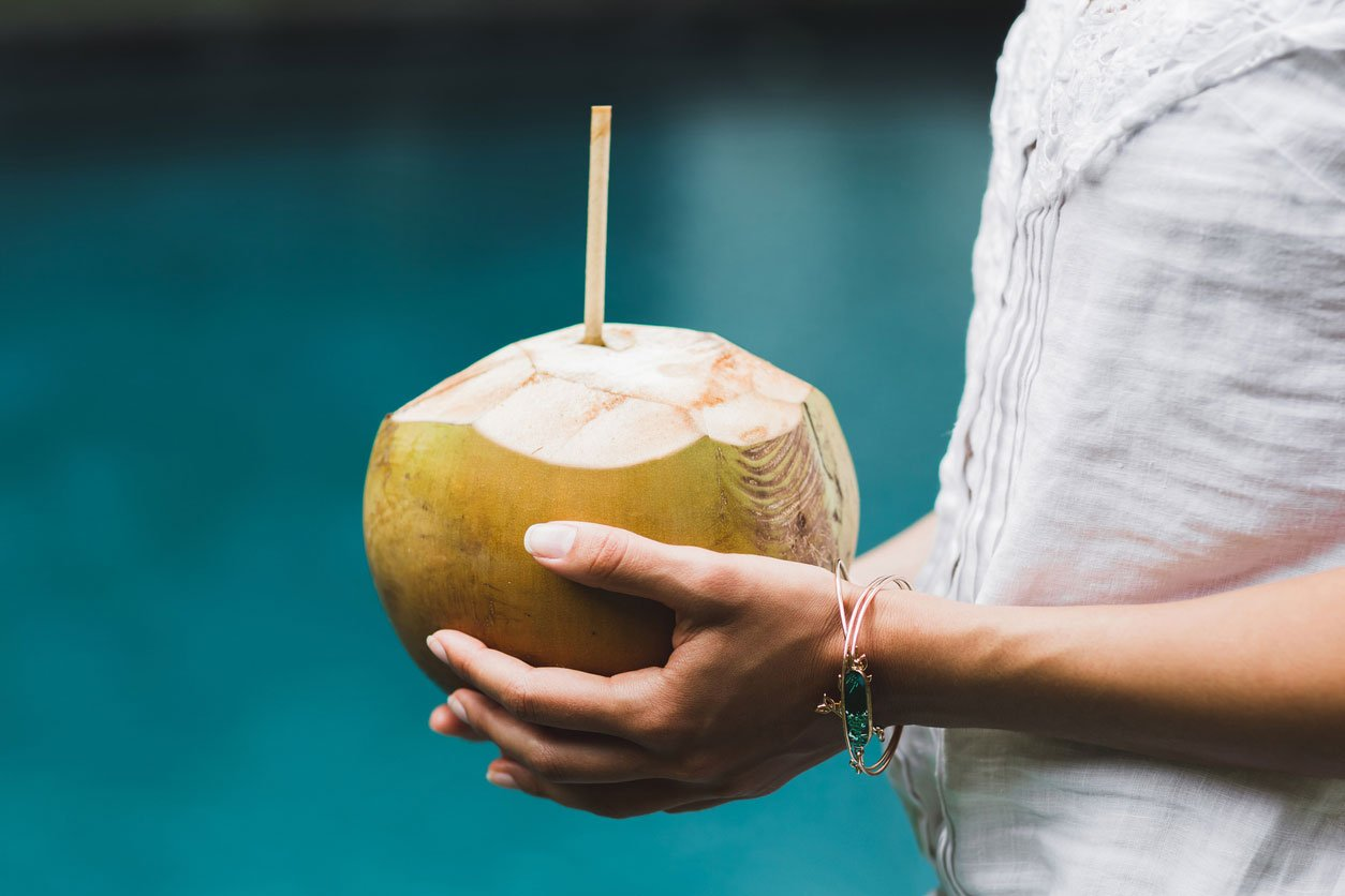 hands holding coconut with straw