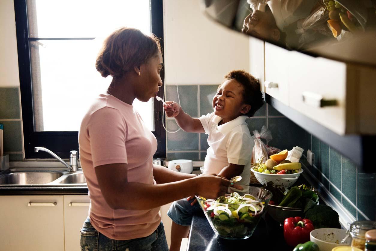 Child feeding mother in kitchen