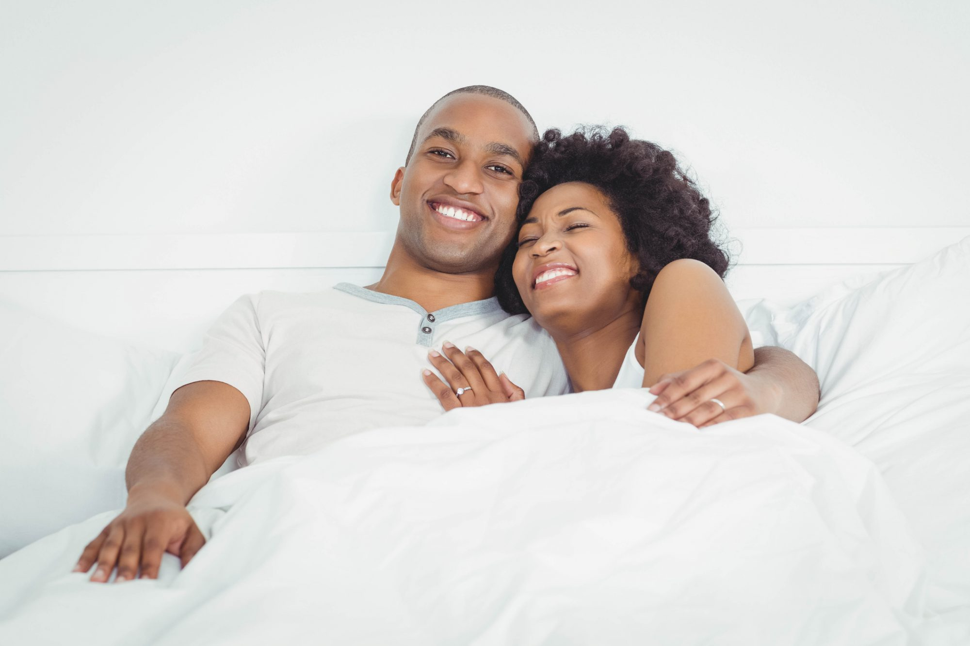 Happy couple on bed laughing