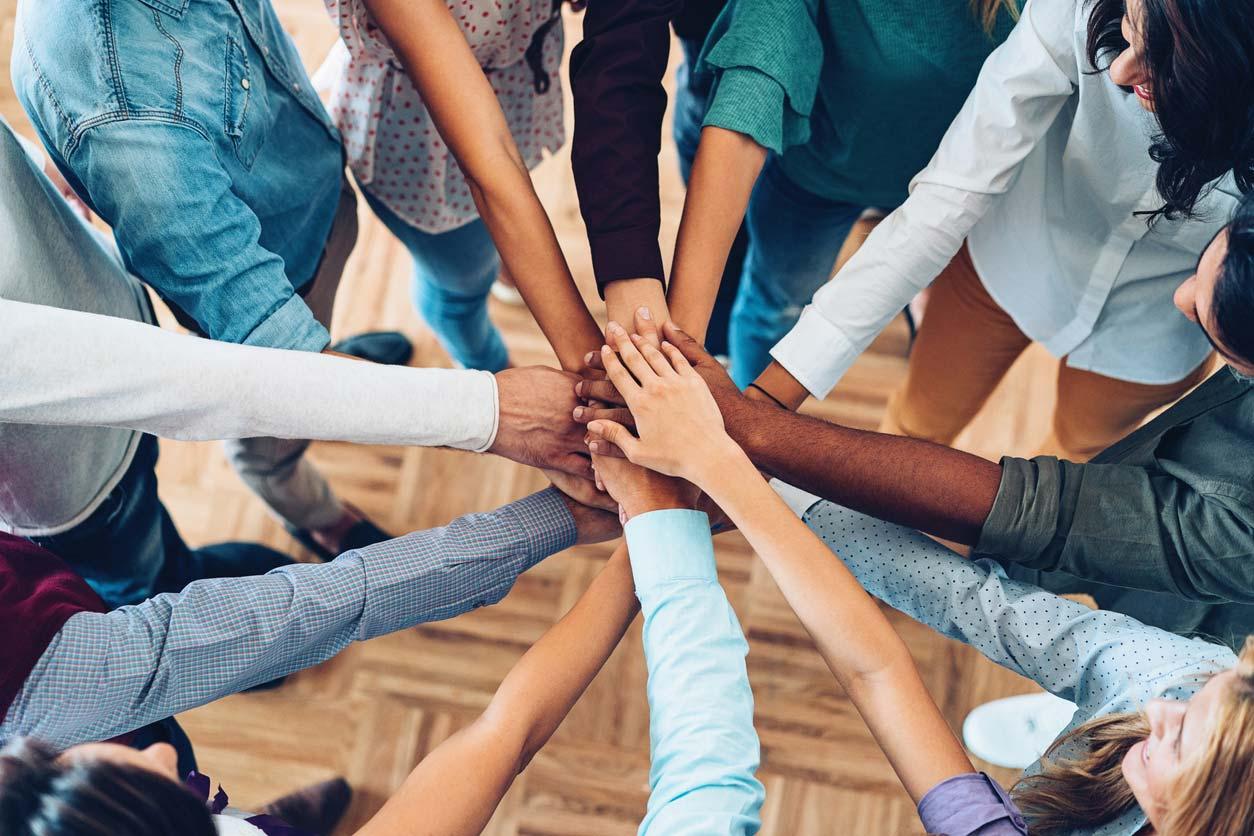 multi-racial hands in circle huddle