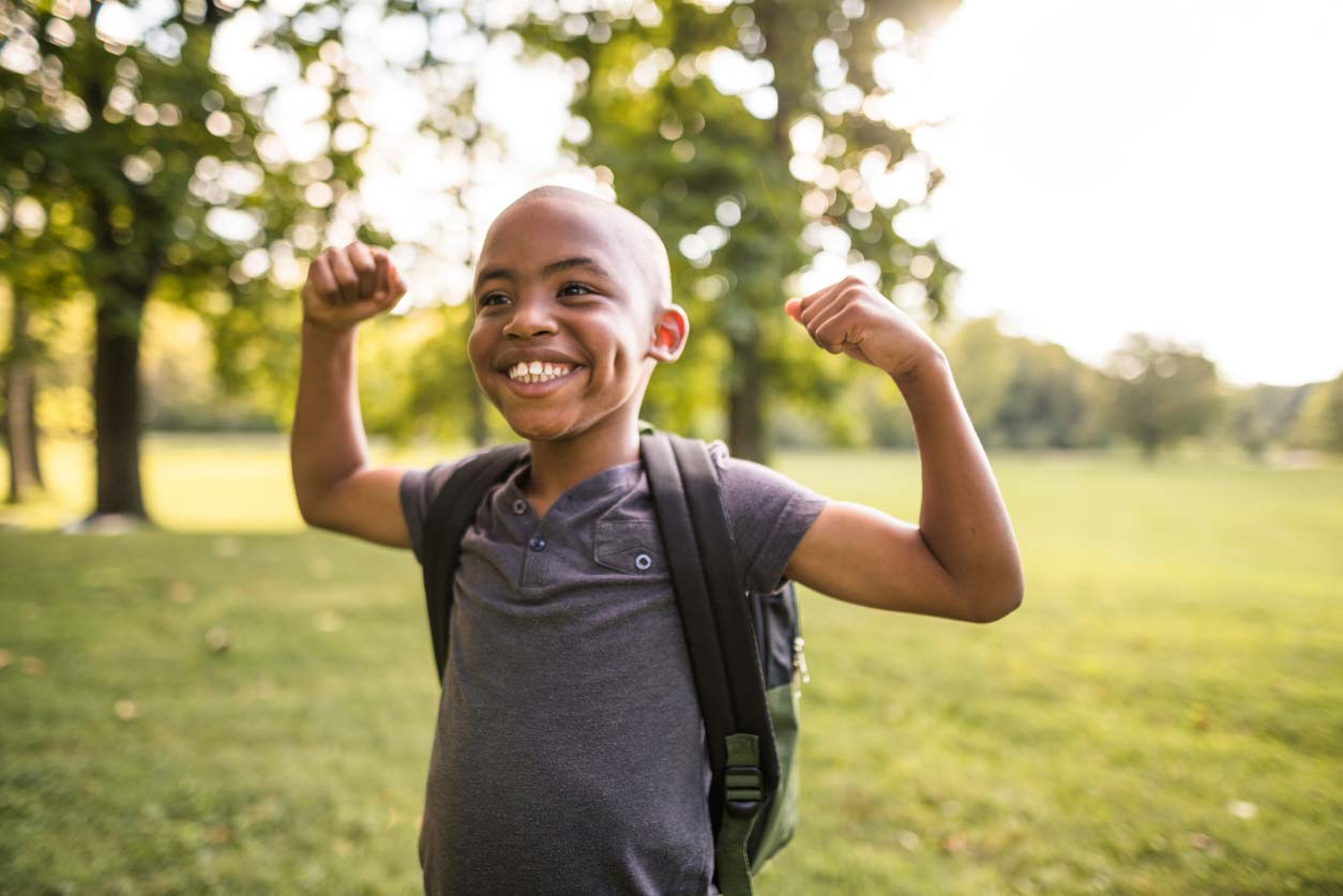 Young boy of color showing his muscles