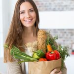 Woman holding a paper bag full of vegetables