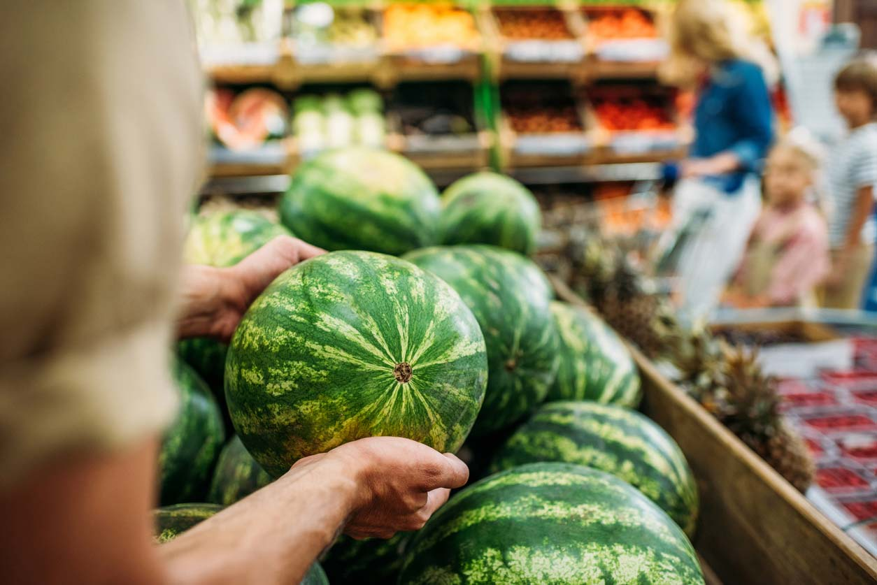 picking a watermelon at the store