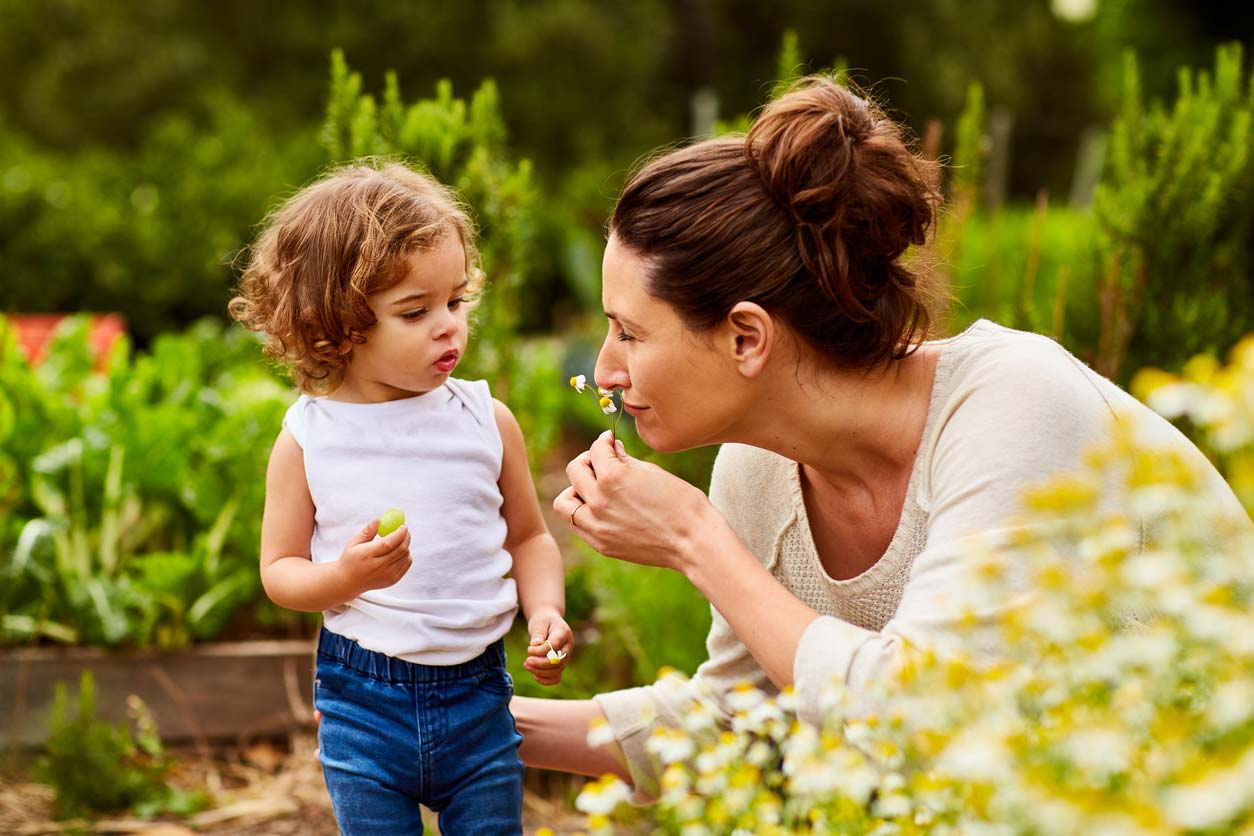 mom and daughter smelling daisies