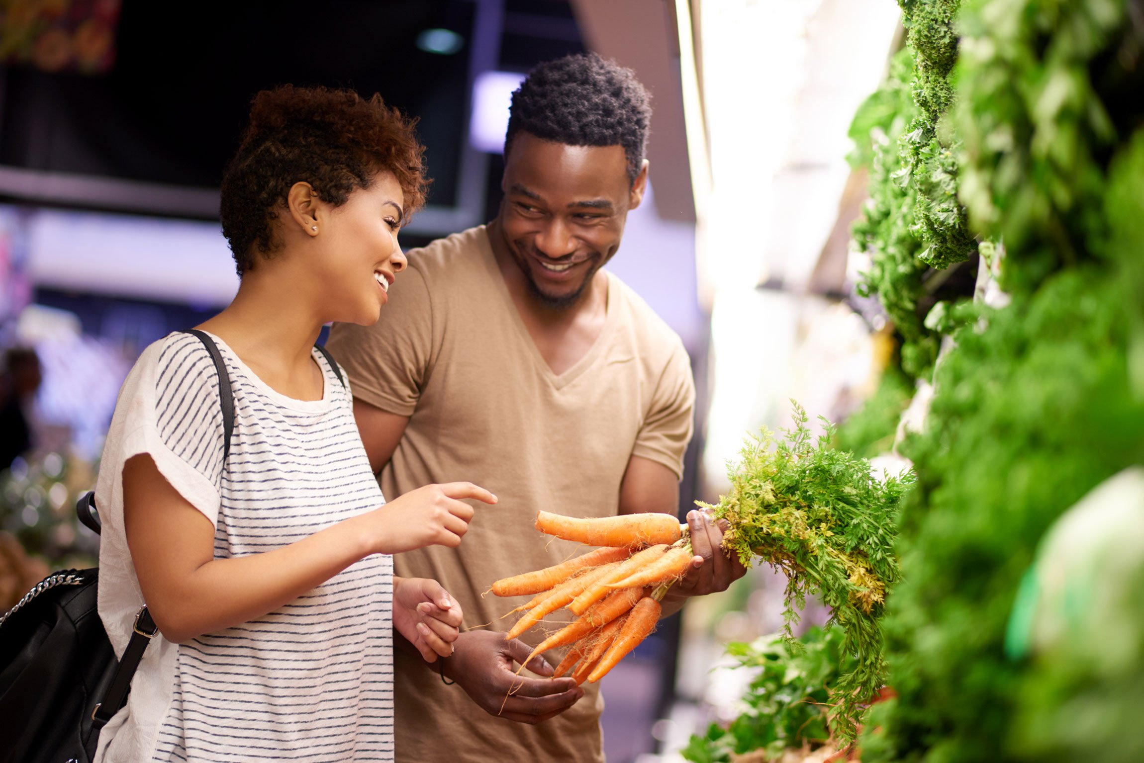 Man and woman looking at carrots in grocery store