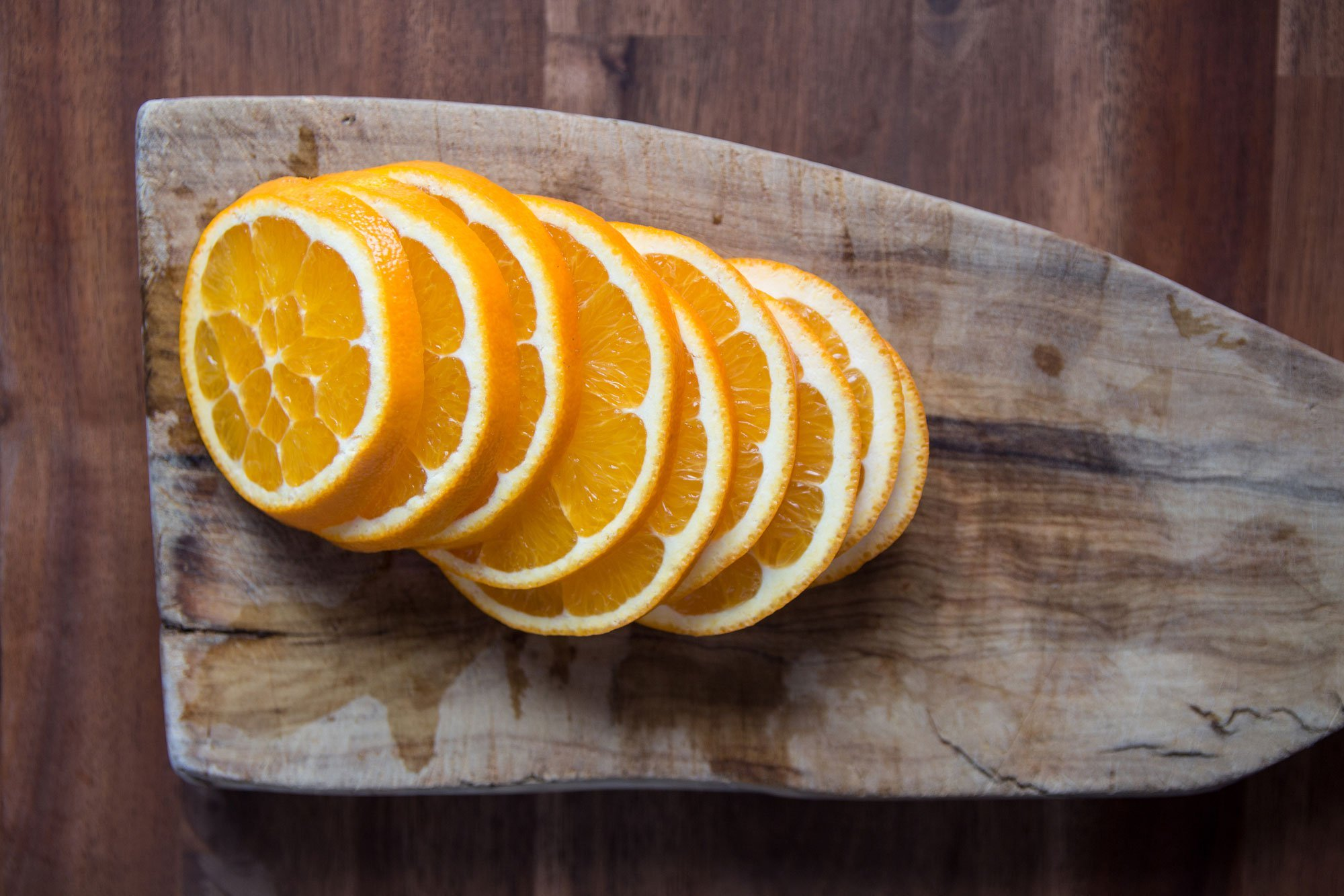 orange slices on wooden cutting board