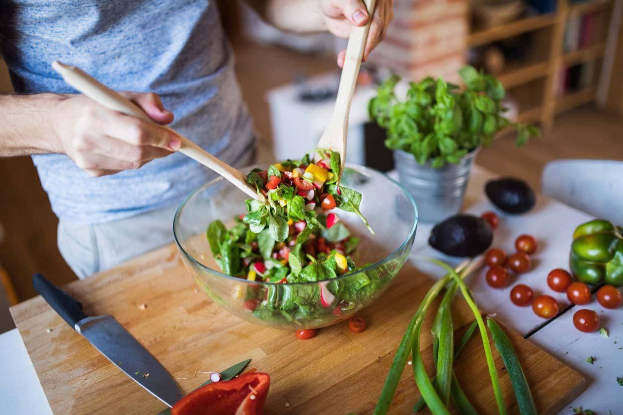 man tossing healthy salad in bowl