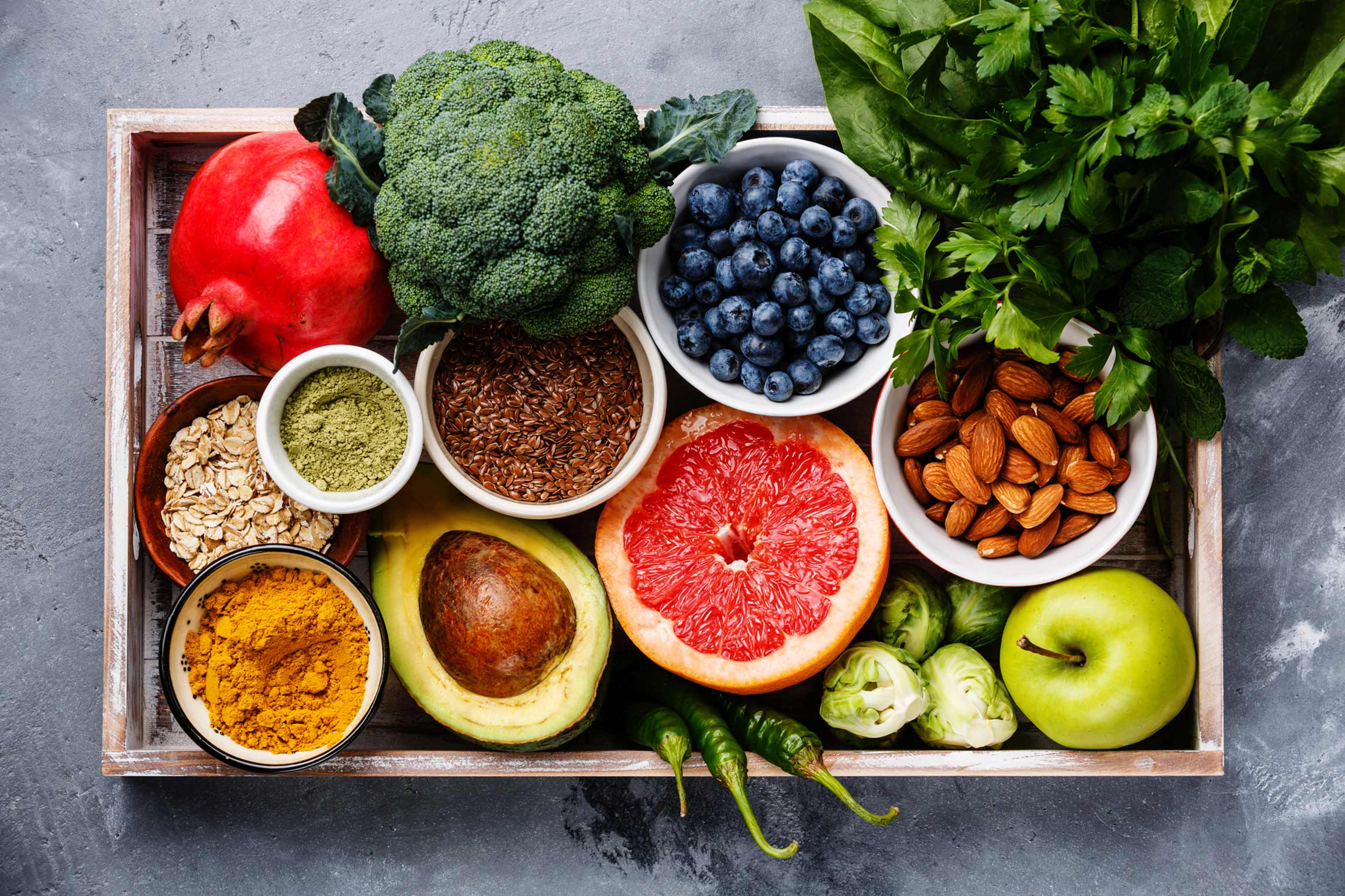 A tray full of fruits, vegetables, nuts, grains, and spices