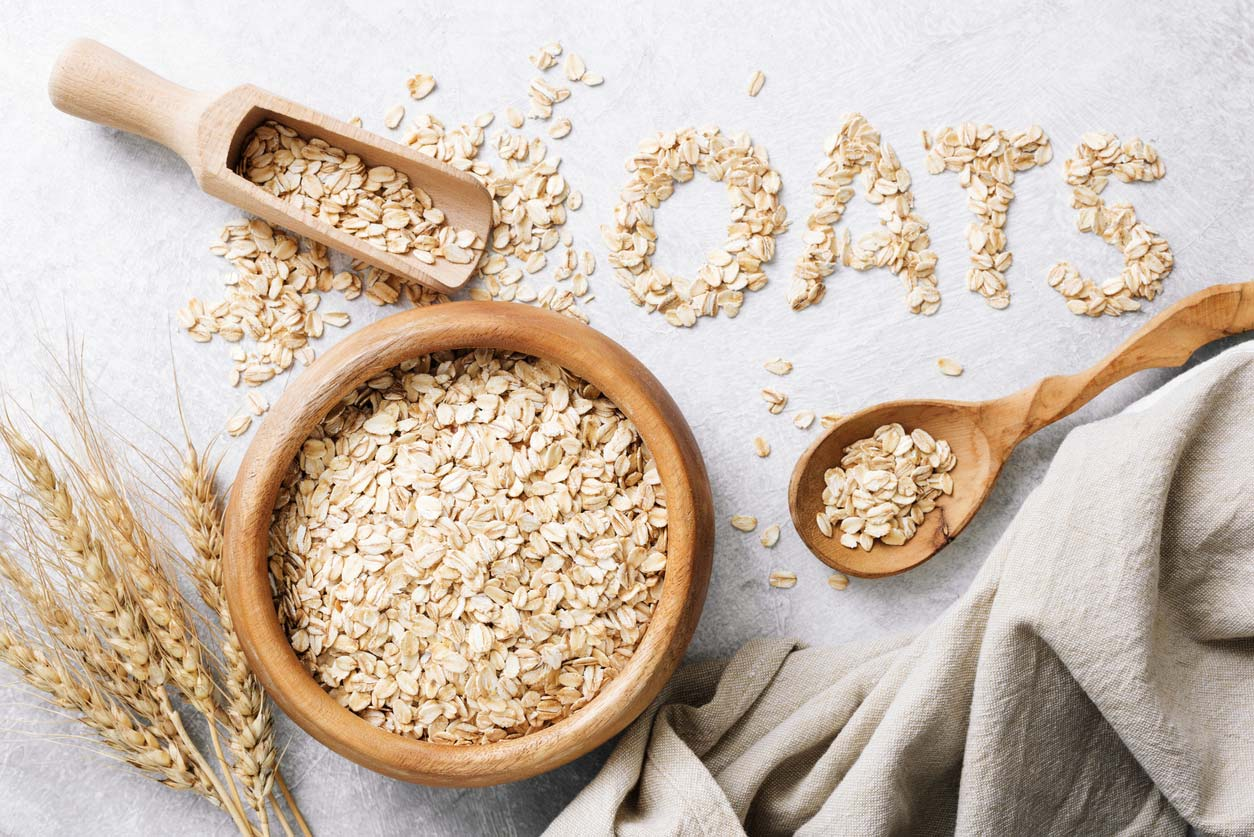 rolled oats in wooden bowl and spelling out the word oats