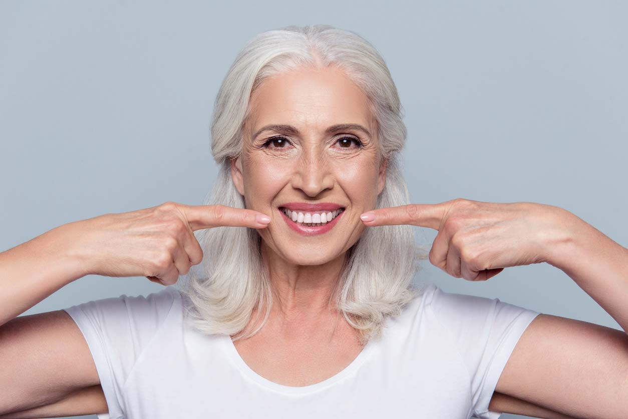 elderly woman pointing to own smiling teeth