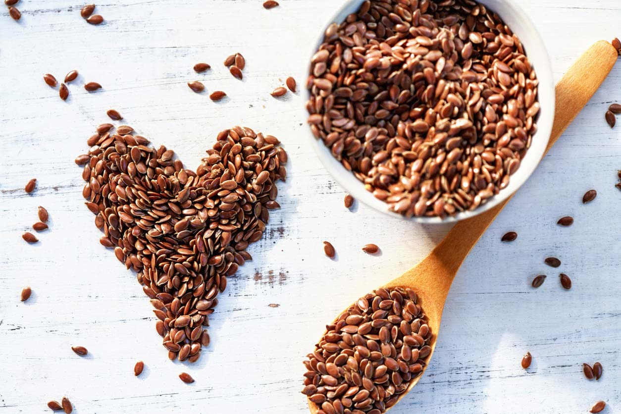 flaxseeds in bowl and on table in shape of heart