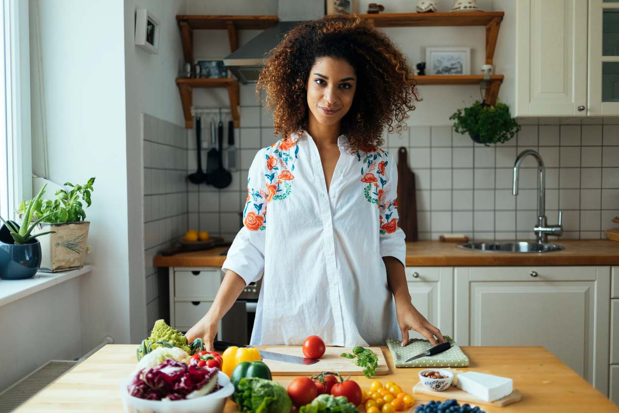 woman at cutting board preparing a raw foods recipe
