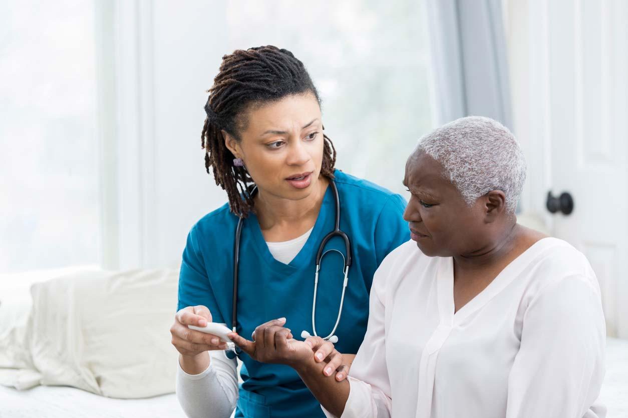 Nurse checks woman's blood sugar