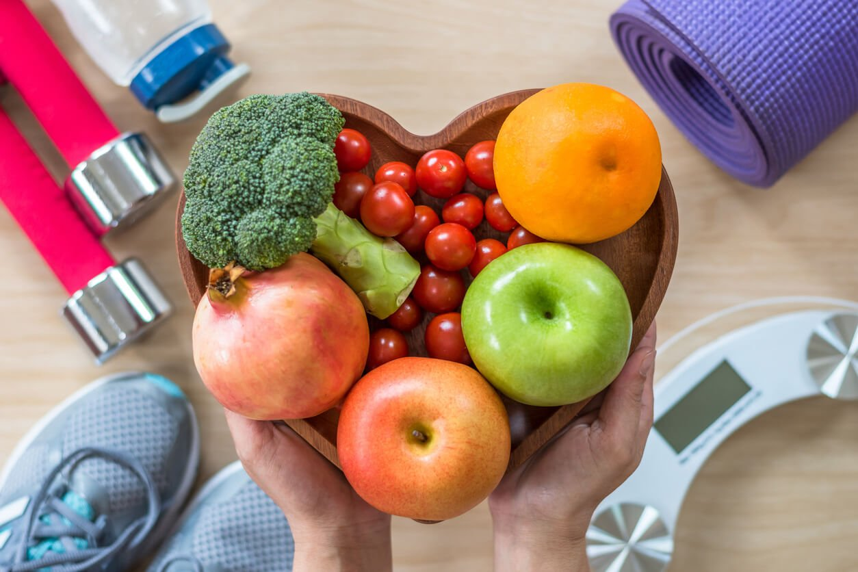 A heart shaped bowl of fruits and vegetables