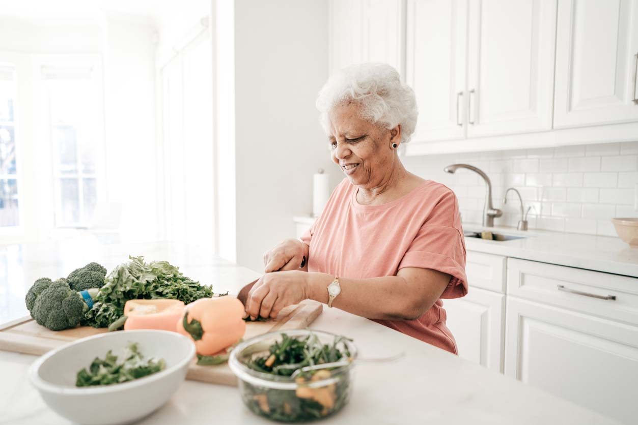 elderly woman preparing green vegetables