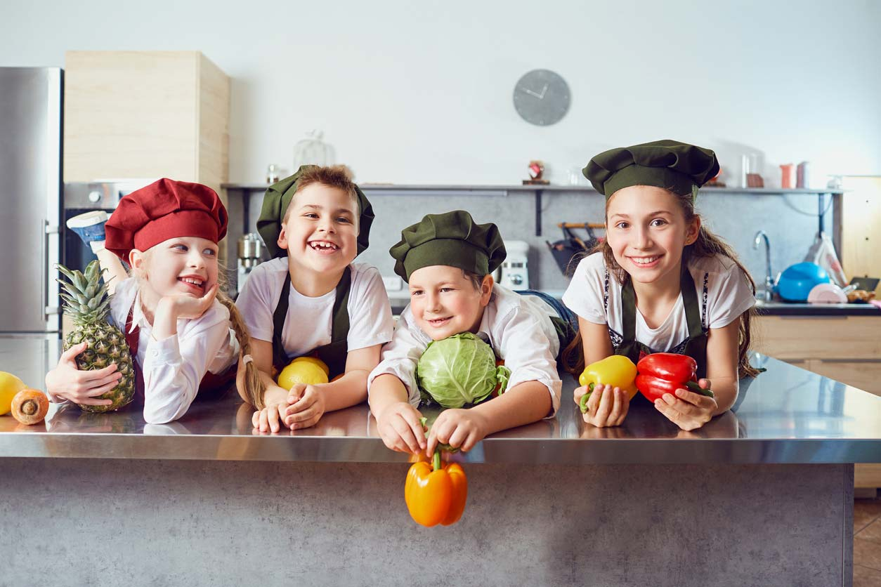 children in chef uniforms holding healthy foods