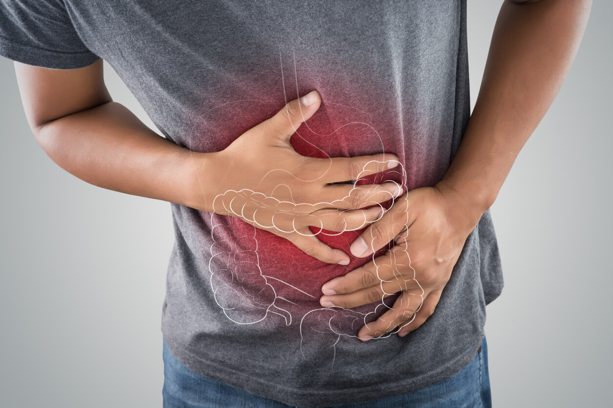 the photo of large intestine on the mans body against a grey background